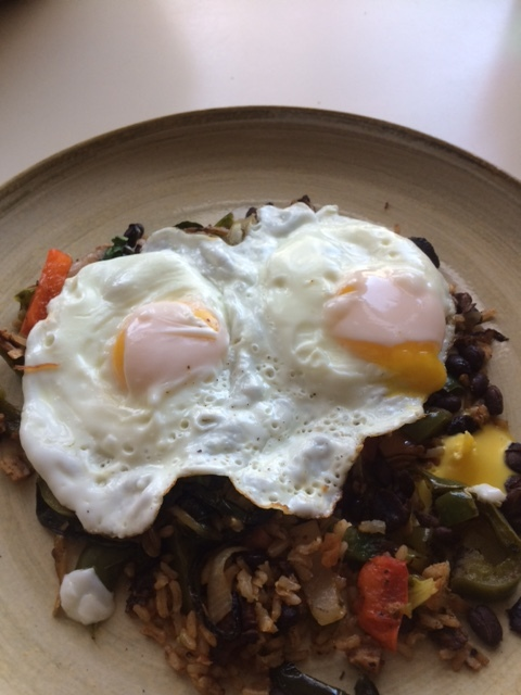 fried eggs over brown rice, black beans and veggies